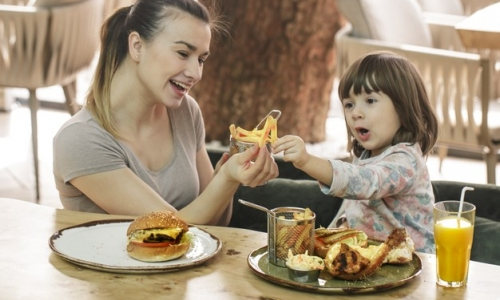 loving-family-mom-with-cute-daughter-eating-fast-food-cafe-family-nutrition-concept_169016-4720